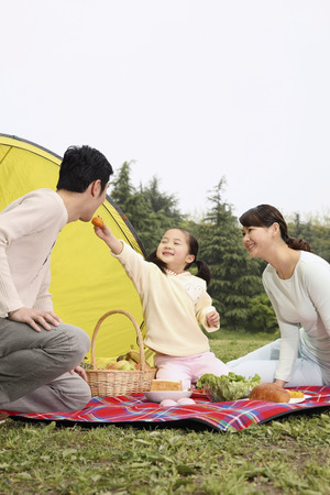 Girl feeding man with biscuit, woman watching photo
