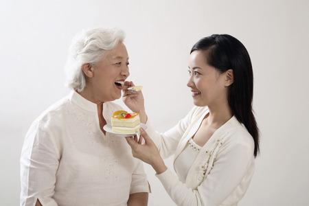 Woman feeding senior woman a slice of cake photo