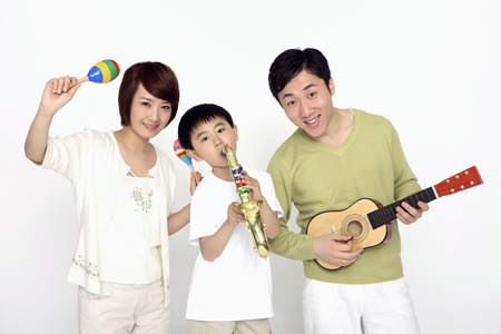 Boy playing musical instrument with his parents