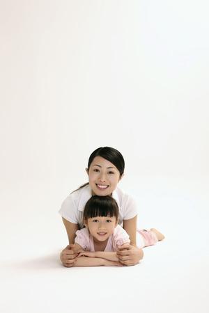 lying forward: Woman and girl lying forward smiling Stock Photo