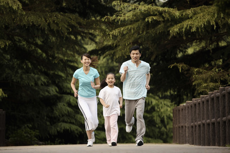 Girl and parents running in the park photo