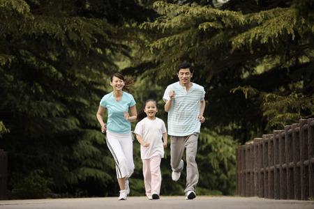 hombres corriendo: Niña y los padres corriendo en el parque