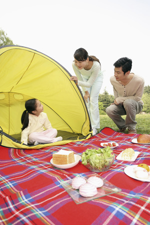 girl squatting: Girl sitting in the tent, man and woman looking at her Stock Photo