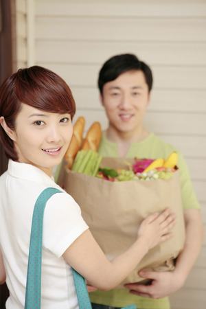 Woman taking grocery bag from man photo