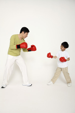 combative sport: Man and boy in red boxing gloves Stock Photo