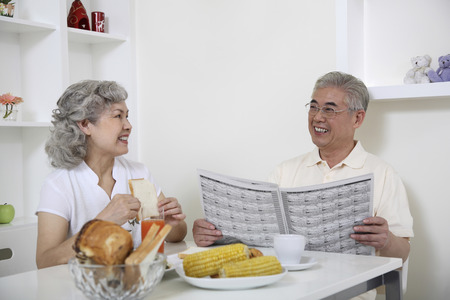 Senior woman talking to senior man while having breakfast Stock Photo - 26203259