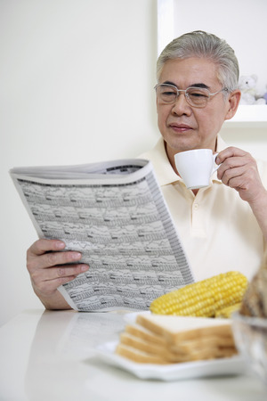 Senior man drinking coffee while reading newspaper photo
