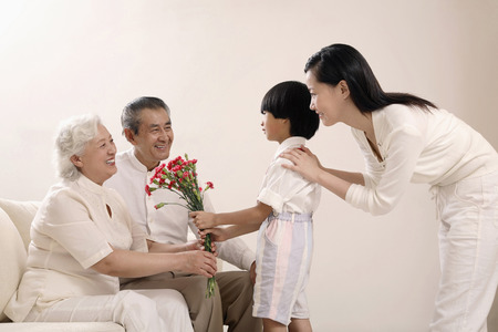 Boy giving a bouquet of flowers to senior woman, woman and senior man watching photo