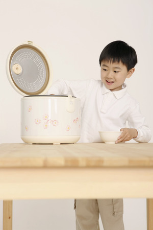 rice cooker: Boy taking rice from rice cooker Stock Photo