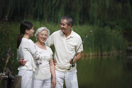 Senior man talking to senior woman and woman while fishing on a dock photo