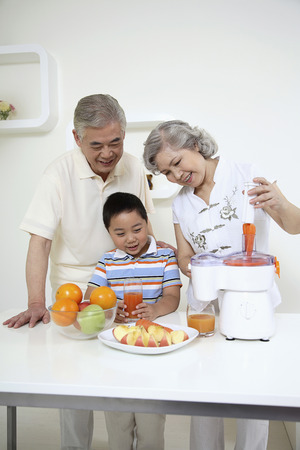Senior woman putting carrots into juicer, boy and senior man watching photo