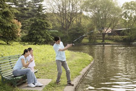 Homme de pêche au bord du lac, femme et fille en regardant