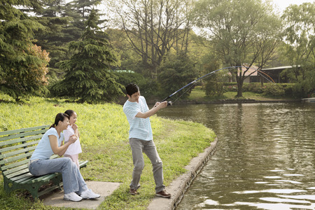 Man fishing by the lakeside, woman and girl watching