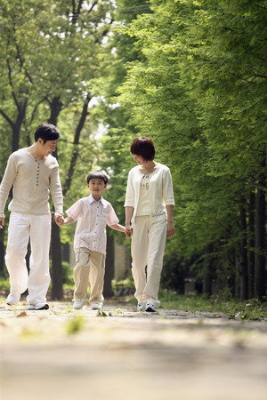Boy holding hands with parents while walking in the park photo