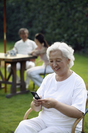 Senior woman text messaging on the phone, woman having tea with senior man in the background Stock Photo - 26202397