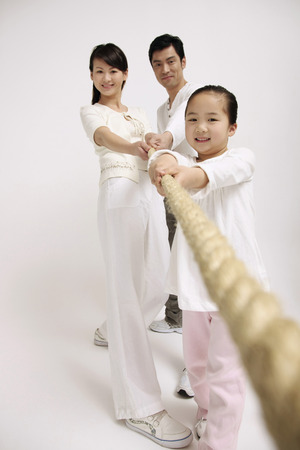 Girl pulling rope with the help of her parents photo
