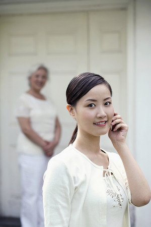 Woman talking on the phone, senior woman standing in the background photo