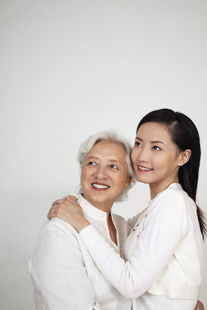 Woman and senior woman smiling while looking up