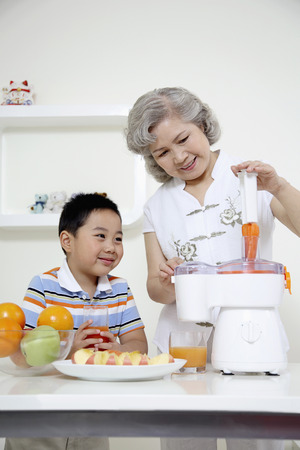 Senior woman putting carrots into juicer, boy watching photo