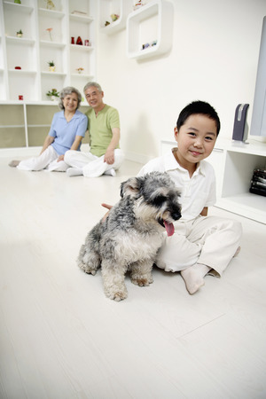 Boy posing with dog, senior man and senior woman watching photo