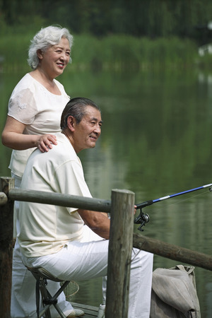 Senior man fishing on a dock, senior woman standing beside him photo
