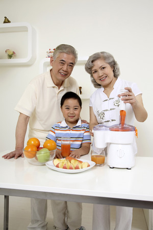 Senior man and senior woman preparing fruit juice for boy photo