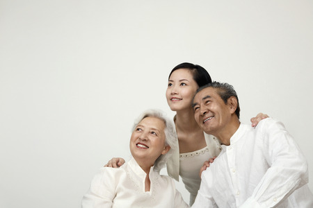 Woman and senior couple smiling while looking away Stock Photo