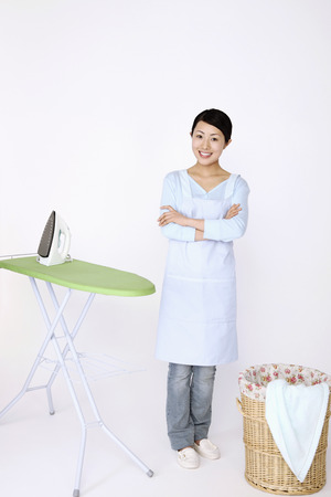 Woman wearing apron with arms crossed smiling photo
