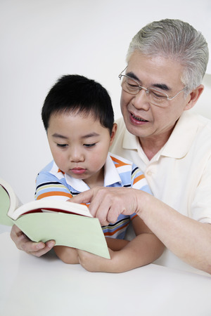 Senior man and boy reading book together Stock Photo - 26200502