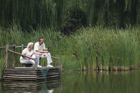 man fishing: Pareja de ancianos sentados en un muelle, juntos de pesca