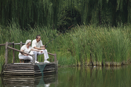 Senior couple sitting on a dock, fishing together photo