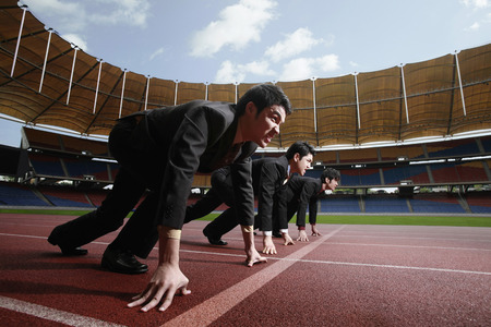 starting a business: Businessmen on starting line of running track Stock Photo