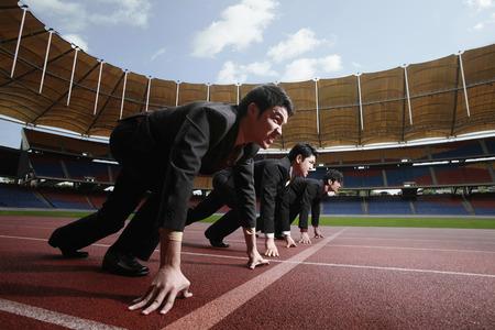 pista de atletismo: Hombres de negocios en l�nea de salida de pista de atletismo