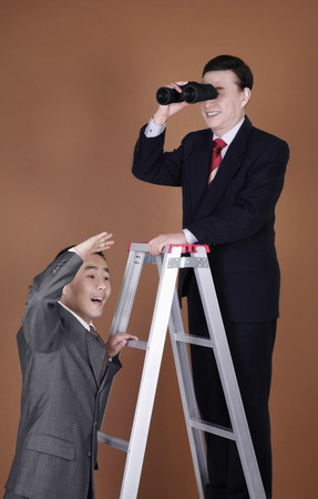 Businessmen on corporate ladder doing observation photo
