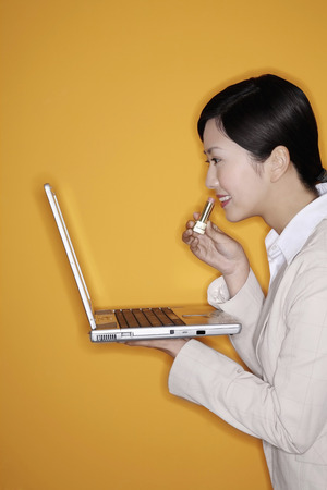 Businesswoman holding laptop and putting on lipstick photo