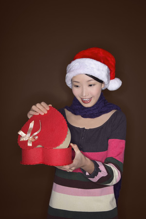 cappello natale: Donna con cappello di apertura regalo di Natale Archivio Fotografico
