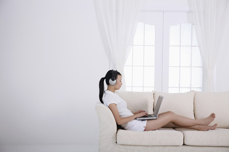Woman with headphones sitting on the couch, using laptop photo
