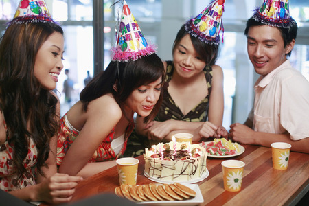 Woman blowing candles on cake, friends watching Stock Photo