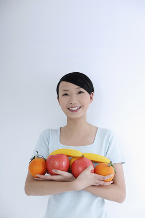 armful: Woman with an armful of fruits