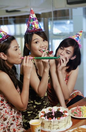 Women blowing party horn blower photo