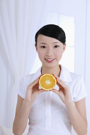 halved: Woman holding halved orange
