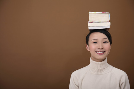 Woman balancing stacked books on her head photo