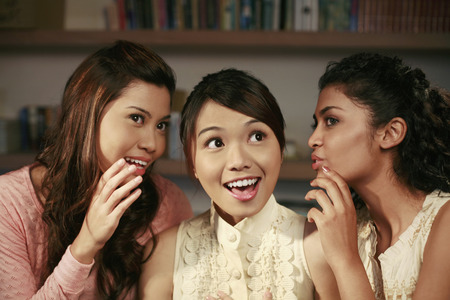 rumours: Women whispering into friends ears