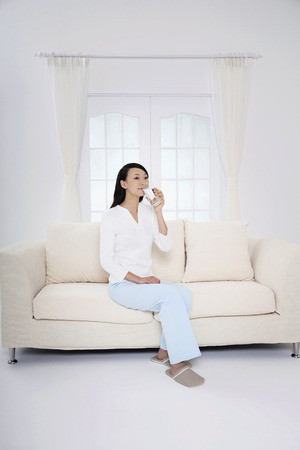 Woman sitting on the couch, drinking a glass of water photo