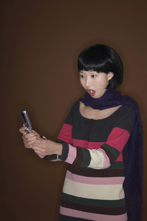 mouth opened: Woman reading text message on her phone with her mouth opened Stock Photo