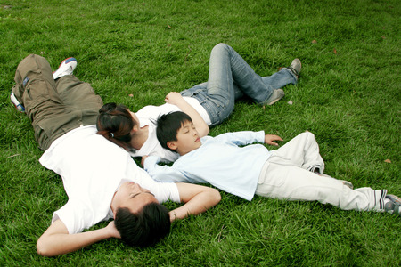 he   my sister: A boy lying on the grass together with his parents