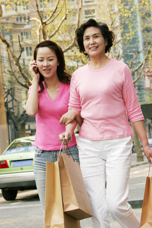 A lady talking on the hand phone while walking with her mother on the street photo