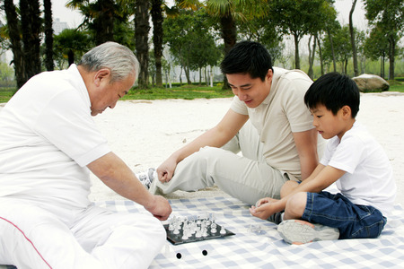 A boy playing chess with his grandfather on the lakeside while his father is watching