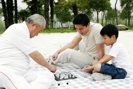 jugando ajedrez: Un niño jugando al ajedrez con su abuelo en la orilla del lago, mientras su padre está mirando