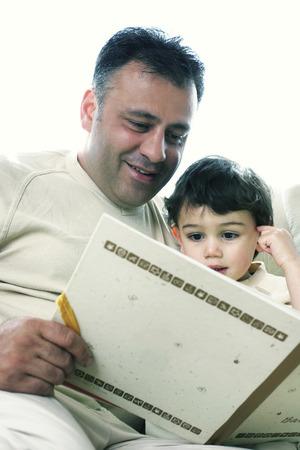 A man reading a book for his son photo